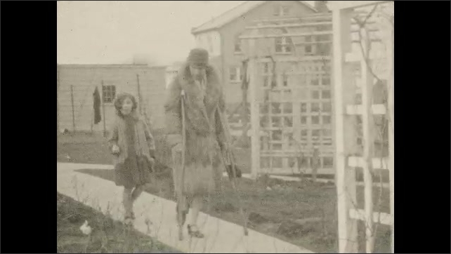 1930s: Windows of a house, a girl walks in the yard next to a woman who walks on crutches, they walk through a garden arch, the girl shows something and smiles, they walk away.