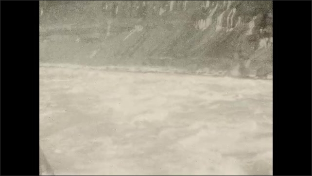 1930s: View of fog that comes out from the Niagara Falls from inside a car that moves. Small birds fly over water from Niagara River that flows fast. Niagara River rapids.
