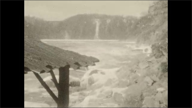 1930s: Cable car lift. The shore of Niagara River with rocks and a hut. Niagara River rapids, a train moves on top of the Suspension Bridge.