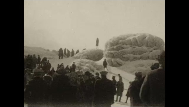 1930s: Frozen rocks on the shore of the Niagara River with Niagara Falls Suspension Bridge. People stand on the ice near the waterfall and watch the falls. Men slide on ice. People walk on the ice.