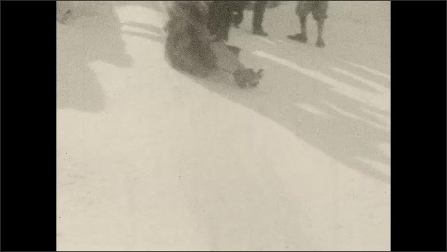 1930s: People stand on top of an ice mound, a woman sits on the ice and prepares to slide. People sit on ice and slide down. Man sits on ice and slides down. Woman sits on ice and slides down.
