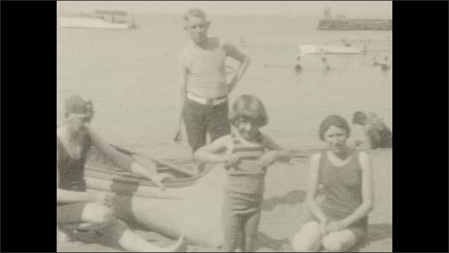 1920s: Beach.  Family poses.  Man lifts child.