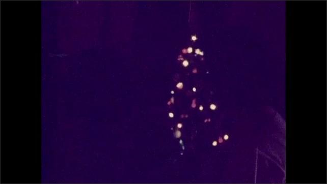 1930s: UNITED STATES: indoor tree. Lights on Christmas tree. Fairy lights on tree.
