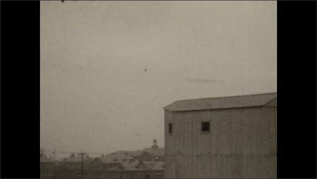 1920s: Sky.  Factories.  Blimp.