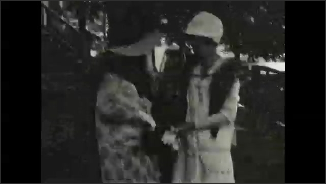 1930s: UNITED STATES: man helps ladies down from car. Men in suits. Family visit.
