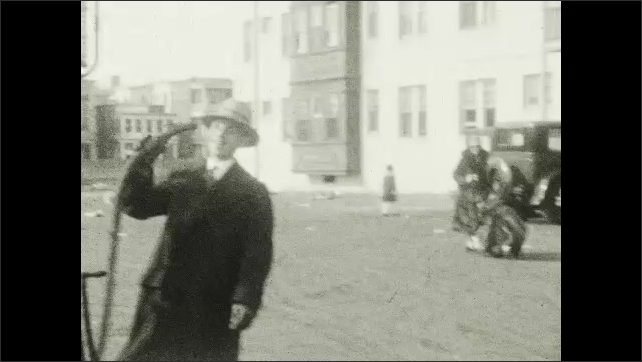 1920s: UNITED STATES: ladies in fur coats walk from cars. Lady holds child's hand. Man carries child in street.
