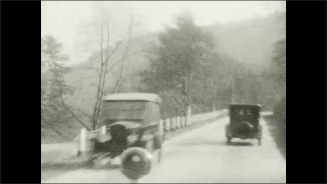 1920s: UNITED STATES: view of road through windscreen of automobile. Cars on road. Bend in road