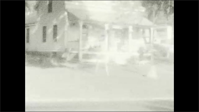 1920s: UNITED STATES: toddler looks at camera and smiles. House and yard in summer. View along country road. Car drives onto street