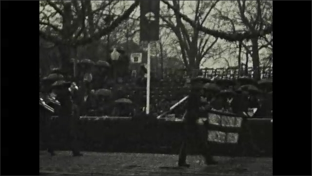 1920s: Parade.  Spectators.  Marching band.  Men carry flags and banner.
