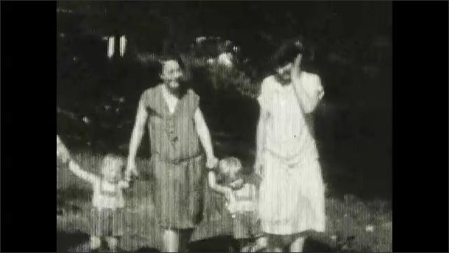 1920s: Lake.  People cross unstable bridge.  Women hold hands with children.