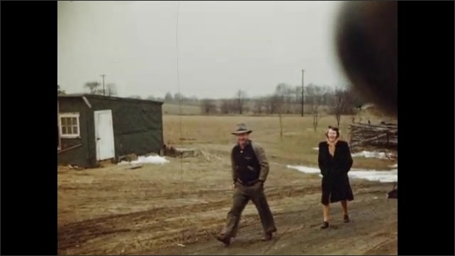 1940s: family walking in a line along a fence, man and woman walking, man takes horse from stable, man gets on horse and is led by another man