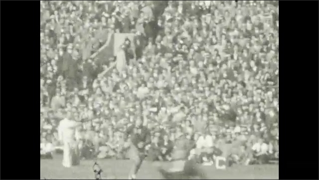 1930s: Cheering crowds at a college football game. Football players on the field playing.