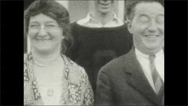 1920s: UNITED STATES: family smile at camera outside home. Family stand for camera in garden
