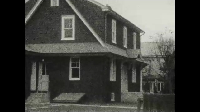 1920s: UNITED STATES: family stand outside house in street. Family stand by fence. Car outside house