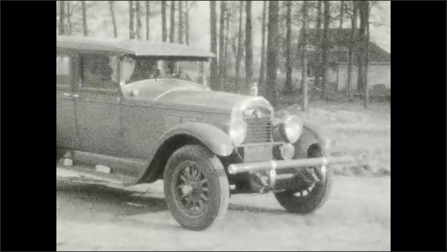 1920s: UNITED STATES: car reverses onto street. Lady in car. Girl and lady in car