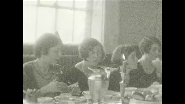 1920s: UNITED STATES: ladies enjoy meal together at table. Lady looks at camera