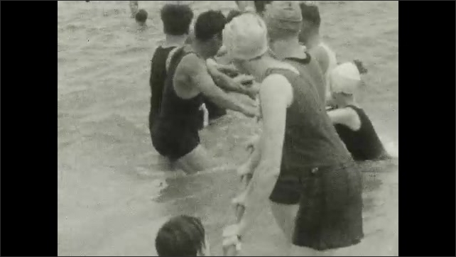 1920s: UNITED STATES: swimmers hold on to rope at seaside. Swimmers jump waves at beach.