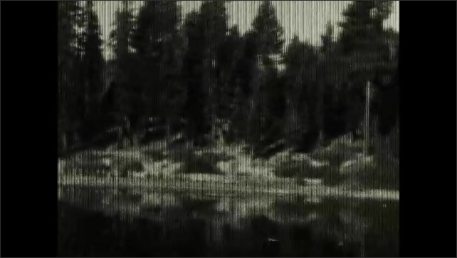 """1920s: View of water from dock. Boat with name """"Tahoe"""" on side. Panorama of lake. House at shore. Woman and child walk in front of building."""