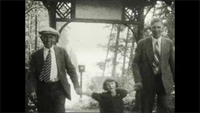 1920s: Sign for Grouse mountain. Large wooden building. Two men walk through archway with little girl. Little girl looks out car window. Lake and mountains.