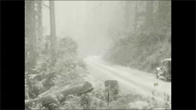 1920s: Water flows down rocks into pool. Cars drive on road through trees.