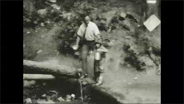 1920s: Buildings. Sign. Man and girl fill cups with water from log.