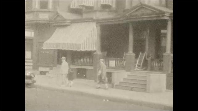 1920s: Men play football. Woman talks. Man drives car, talks. Women stand on porch, walk down steps, get into car. Rowhomes.