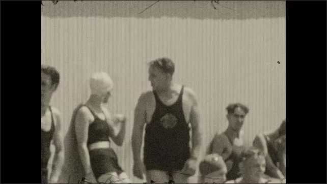 1920s: People dive into pool, swim in pool. People stand by pool, sit on benches by pool.