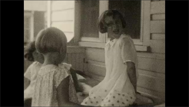 1920s: Woman walks outside in garden. Girls play on porch. Man smiles, smokes cigarette.