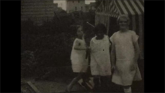 1920s: Girls play outside by playhouse.