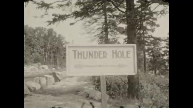 1920s: Car drives down coastal road lined with pine trees. Woman poses next to Thunder Hole sign. Women and men walk on rocks next to Thunder Hole next to the ocean.