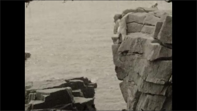 1920s: Man climbs on steep rock face next to ocean.
