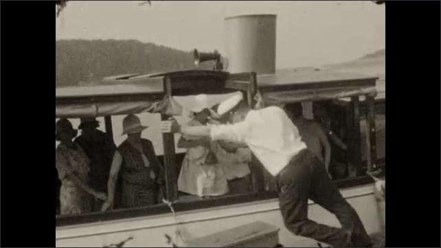 """1920s: Boat pulls up to dock marked """"Sight-seeing boat"""". Women, men and children are helped off of the boat. Captain adjusts the boat so girl can get off. Two men and woman walk up dock."""