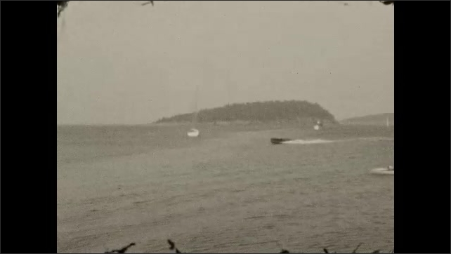 1920s: Man rows rowboat with two women in it next to pier. Motor and sailboats on the water.