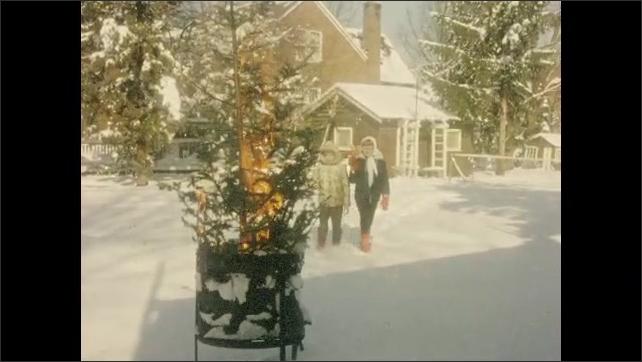 1950s: Little girls walk across snowy yard holding dolls.  Tree burns in trash can.