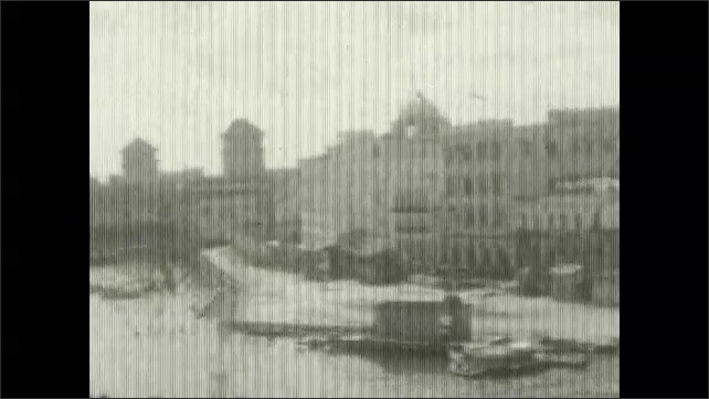 1920s: UNITED STATES: boat travels along dock. Harbour view from boat. Buildings in port.