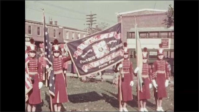 1920s: City street, rowhouses, parade route turns corner. Man in Native American headdress salutes. Marching band in uniform holds banner, man in military dress uniform. Women march, carry flags.