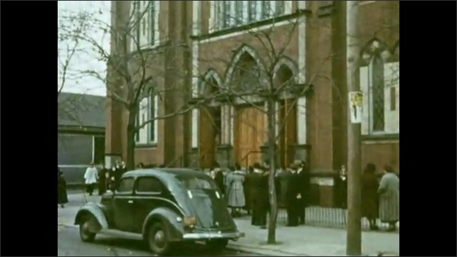 1920s: St. John Cantius church, parked car, people gathered on sidewalk, two tall spires.
