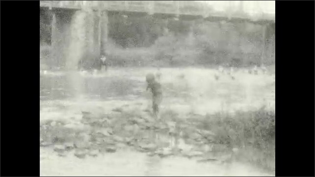 1920s: People play and swim in river near trestle bridge. Children walk along rocks on river's edge. Man watches children wade in shallow water. Man dives from bridge into river.