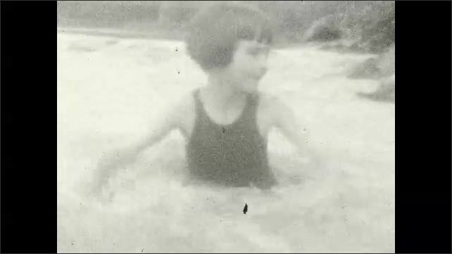 1920s: Large stone bridge over shallow river. Dogs walk  on edge of river. Girls play and splash in river. Dogs and children play in shallow river.