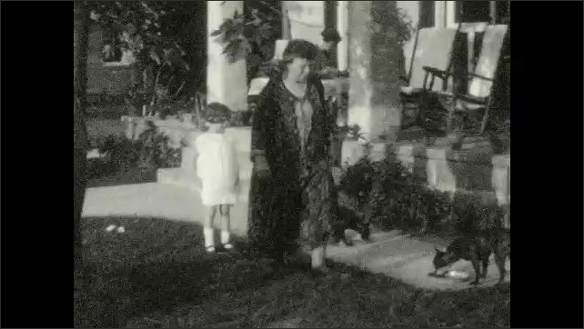 1920s: Women and girl walk around porch. Grandparents, girl and dogs walk around porch. Man and woman sit under tree in lawn chairs. Woman sits on rocking chair. Man dances near woman.