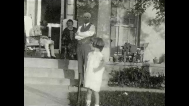 1920s: Man and woman flirt and talk by porch. Man, woman and child pose near porch. Woman and girl pose near house. Women and children wave.