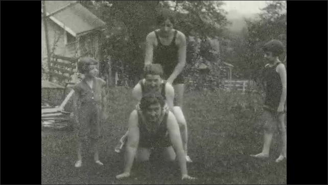 1920s: Woman poses in bathing suit. Women and girl pose in bathing suits. Women and girls form pyramid on lawn. Dogs run around girls and women on lawn. Woman poses in bathing suit.