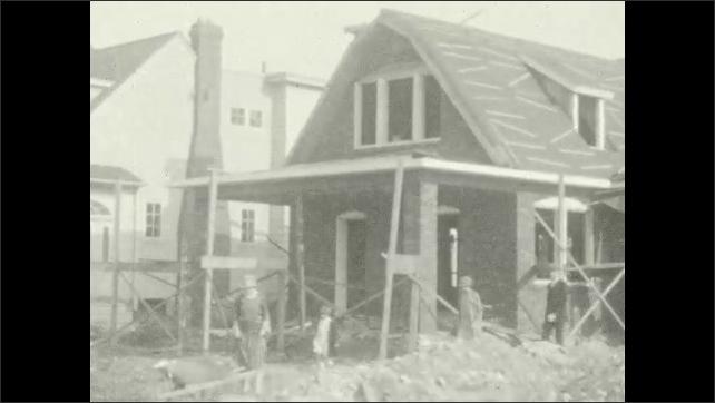 1920s: Bi-plane flies in sky. Family walks around new home construction site. Family enter car near construction site.