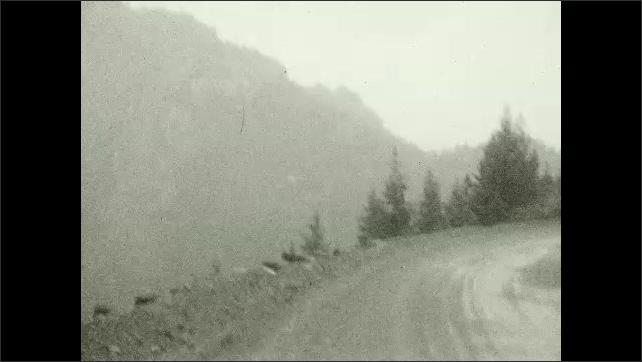 1920s: Road winds through mountains.  Car.  Tunnel cut through rock.
