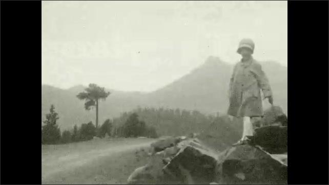 1920s: Mountains.  Dirt road.  Little girl holds umbrella.