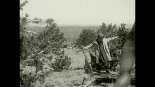 1920s: Car drives down winding mountain road.  Family pose together.  Girl sticks her head out of car window and waves.