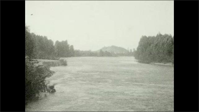 1920s: River, dam. People walking along edge of retaining wall.