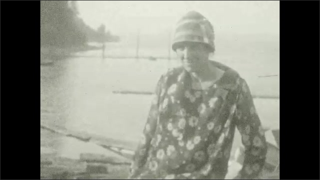 1920s: Man, woman, and girl sit on grass. Woman stands up, man tries to lift woman's dress. Shack on edge of river. Woman stands by river, girl runs up and hugs woman.