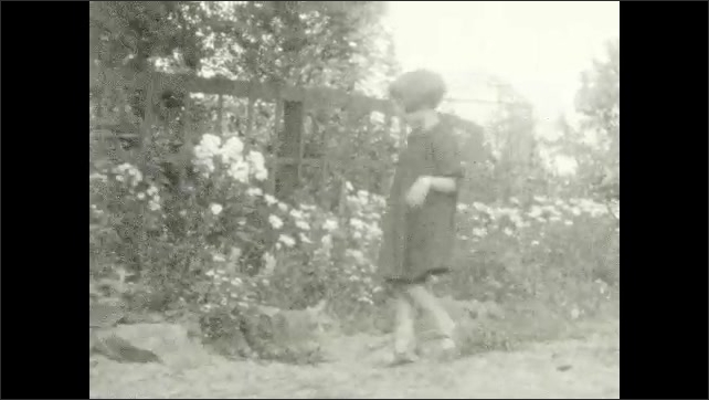 1920s: Woman and girl walk away from riverbank. Man holds tree branch. Girl looks at flowers. City lights.