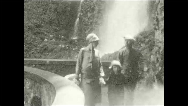 1920s: Girl plays with stick in the woods. Man, woman, and girl walk across bridge in front of waterfall. Mountain, lake, trees. Woman and girl stand in forest, wave.